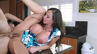 A milf with large tits is getting a dick shoved in her cunt in the kitchen