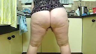 Obese dark brown hair whore cleans the kitchen on web camera
